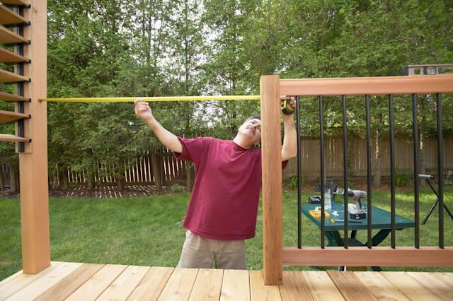 A3J9MY Man Building Deck man; looking; up; 40-50; year; old; people; house; tree; 1; building; construction; home; garden; wood;