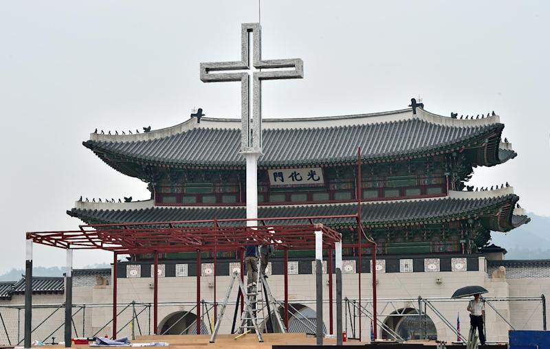 Workers prepare a platform ahead of a special Korean reconciliation mass, to be conducted by Pope Francis, at Gwanghwamun Square in Seoul on August 13, 2014 (AFP Photo/Jung Yeon-Je)