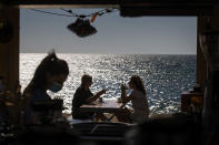 People sit on a terrace in a beach in Barcelona, Spain, on Wednesday, May 27, 2020. Roughly half of the population, including residents in the biggest cities of Madrid and Barcelona, are entering phase 1, which allows social gatherings in limited numbers, restaurant and bar service with outdoor sitting and some cultural and sports activities. (AP Photo/Emilio Morenatti)