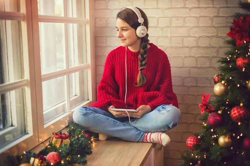 Teenage girl at home for holiday, she sitting by the window using digital tablet and listening to music in cozy Christmas atmosphere