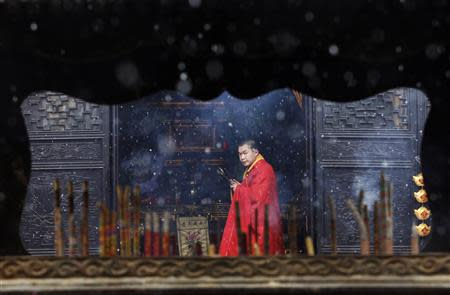 A monk is seen through an incense burner inside a temple as snow falls in Jiaxing, Zhejiang province, in this February 19, 2013 file photo. REUTERS/William Hong/Files (CHINA)