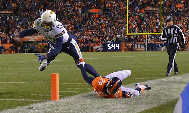 San Diego Chargers wide receiver Keenan Allen (13) stretches the ball across the goal line for a touchdown against Denver Broncos free safety Michael Huff (29) in the fourth quarter of an NFL AFC division playoff football game, Sunday, Jan. 12, 2014, in Denver. (AP Photo/Jack Dempsey)
