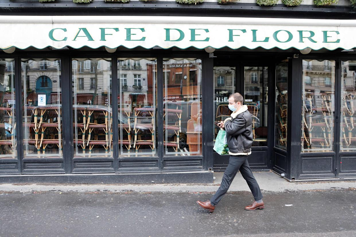 A man wearing a protective face mask walks past famous Cafe de Flore closed along with all cafes and restaurants to curb the spread of the coronavirus, Covid-19, in the Saint-Germain-des-Prés district of Paris on March 15, 2021. (Photo by Ludovic MARIN / AFP) (Photo by LUDOVIC MARIN/AFP via Getty Images)