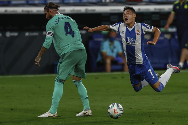 Espanyol's Wu Lei, right, is tackled by Real Madrid's Sergio Ramos during the Spanish La Liga soccer match between RCD Espanyol and Real Madrid at the Cornella-El Prat stadium in Barcelona, Spain, Sunday, June 28, 2020. (AP Photo/Joan Monfort)