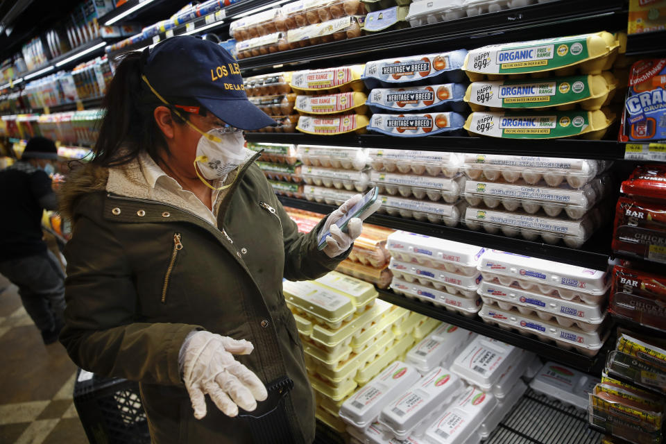 Sandra Perez checks her phone for updates on requests as she shops at a grocery store for goods she intends to donate to needy families, April 18, 2020, in New York City. (AP Photo/John Minchillo)