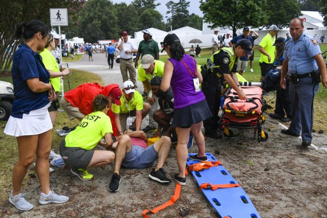 Spectators are tended to after a lightning strike on the course left several injured during an inclement weather delay in the third round of the Tour Championship on Saturday in Atlanta. (Photo/John Amis)