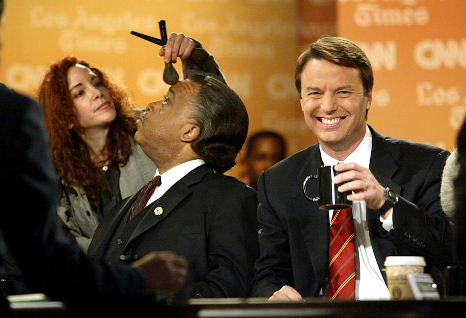 <p>U.S. Senator John Edwards (D-NC) (R) smiles as a make up artist applies make up to the face of Rev. Al Sharpton at the beginning of a debate at the University of Southern California February 26, 2004 in Los Angeles, California. Edwards, Sharpton, U.S. Senator John Kerry (D-MA) and U.S. Congressman Dennis Kucinich (D-OH) are all taking part in the debate. (Photo by Chris Hondros/Getty Images) </p>