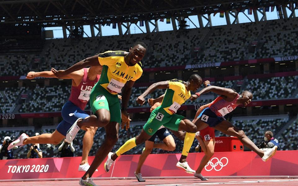 Jamaica's Hansle Parchment (L) crosses the finish line to win ahead of second-placed USA's Grant Holloway (R) and third-placed Ronald Levy - AFP