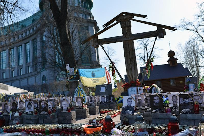 Candles and photographs of people killed during protests in 2014 sit in front of a small wooden chapel built a year ago above the Maidan in Kiev on April 11, 2015 (AFP Photo/Genya Savilov)