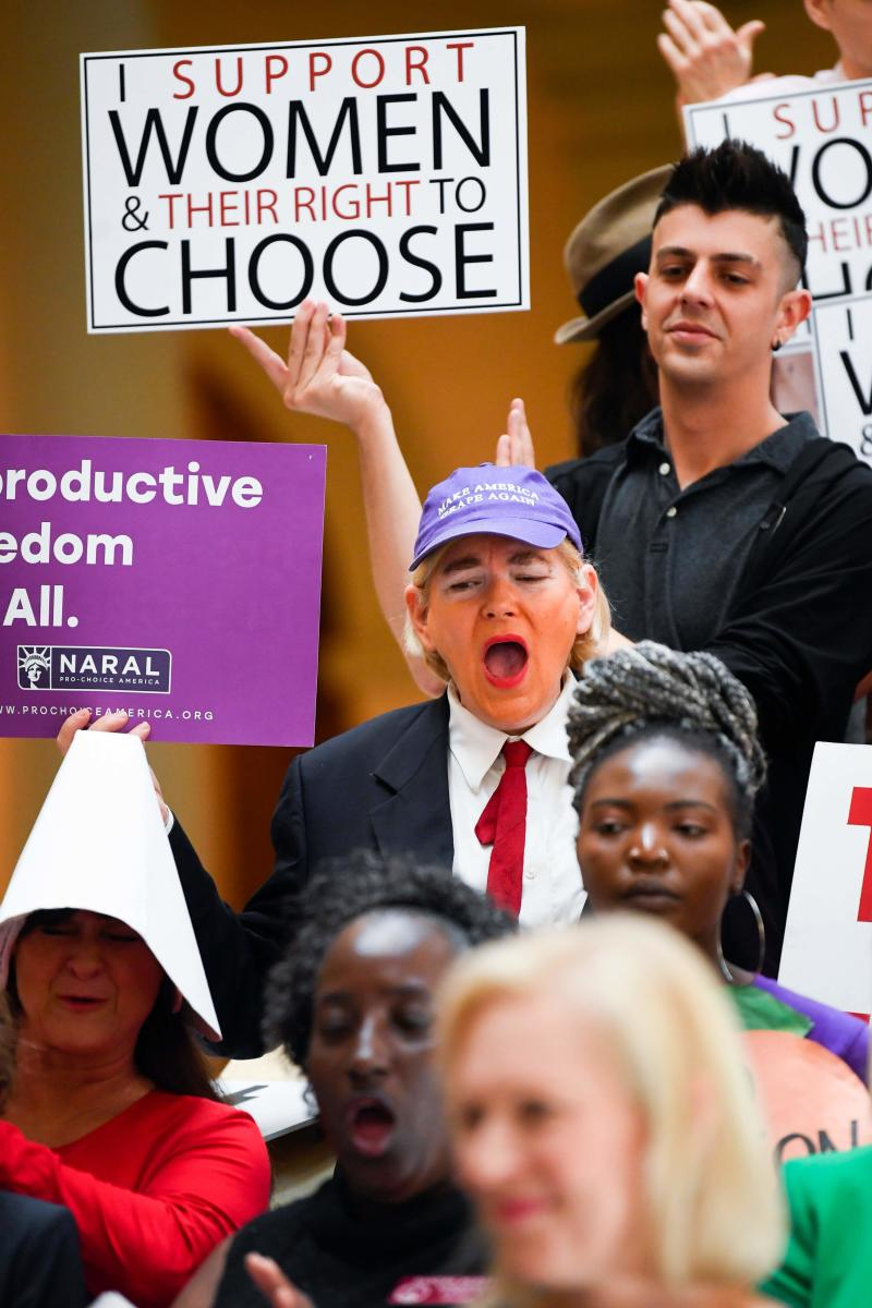 """An activist made up in the likeness of the US president listens as Democratic presidential candidate Sen. Kirsten Gillibrand (D-NY) addresses an event at the Georgia State Capitol to speak out against the recently passed """"heartbeat"""" bill on May 16, 2019 in Atlanta, Georgia."""