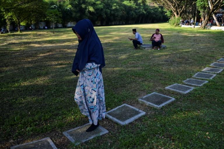 Many people who lost loved ones in the disaster do not know where they were buried. Here, a woman walks past people praying at a cemetery containing mass graves in Siron, in Indonesia's Aceh province (AFP Photo/CHAIDEER MAHYUDDIN)