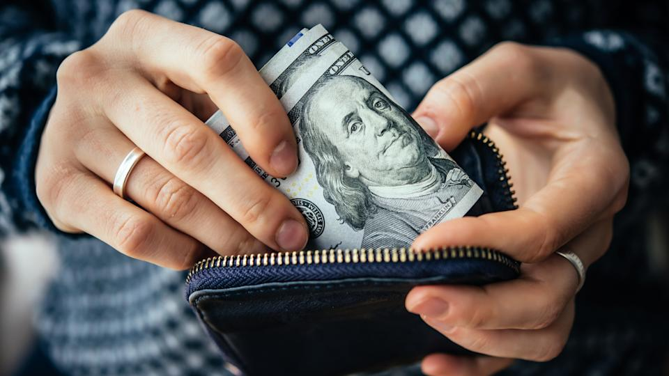 woman taking cash out of wallet