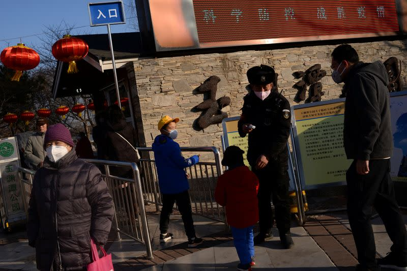 Security personnel checks temperatures of visitors entering the Yuyuantan Park, as the country is hit by an outbreak of the new coronavirus, in Beijing
