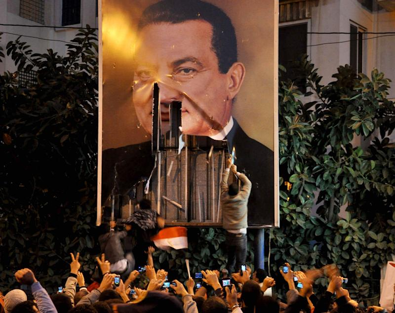 FILE - In this Tuesday Jan. 25, 2011 file photo, Demonstrators deface a poster of  Egyptian President Hosni Mubarak in Alexandria, Egypt. More Arabs are politically engaged than ever before, demanding to be heard. They're learning what it means to question everything and everyone after decades under heavy autocracies where discussion, innovation and public participation were discouraged or crushed. This week, as Egyptians prepare to mark on Friday the anniversary of the start of the revolution that swept aside Hosni Mubarak, the issue seems to come up at every panel that even tangentially touches on politics or strategy. (AP Photo, File)