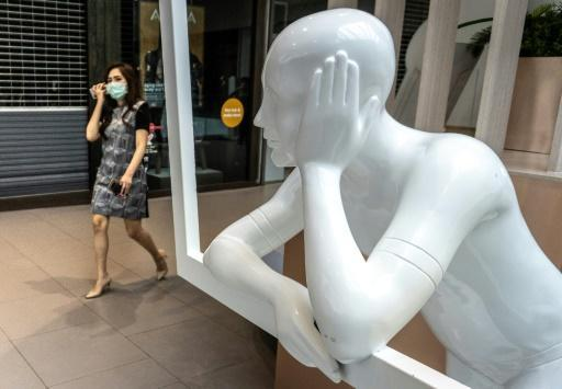 A woman wearing a face mask enters a shopping mall in Bangkok