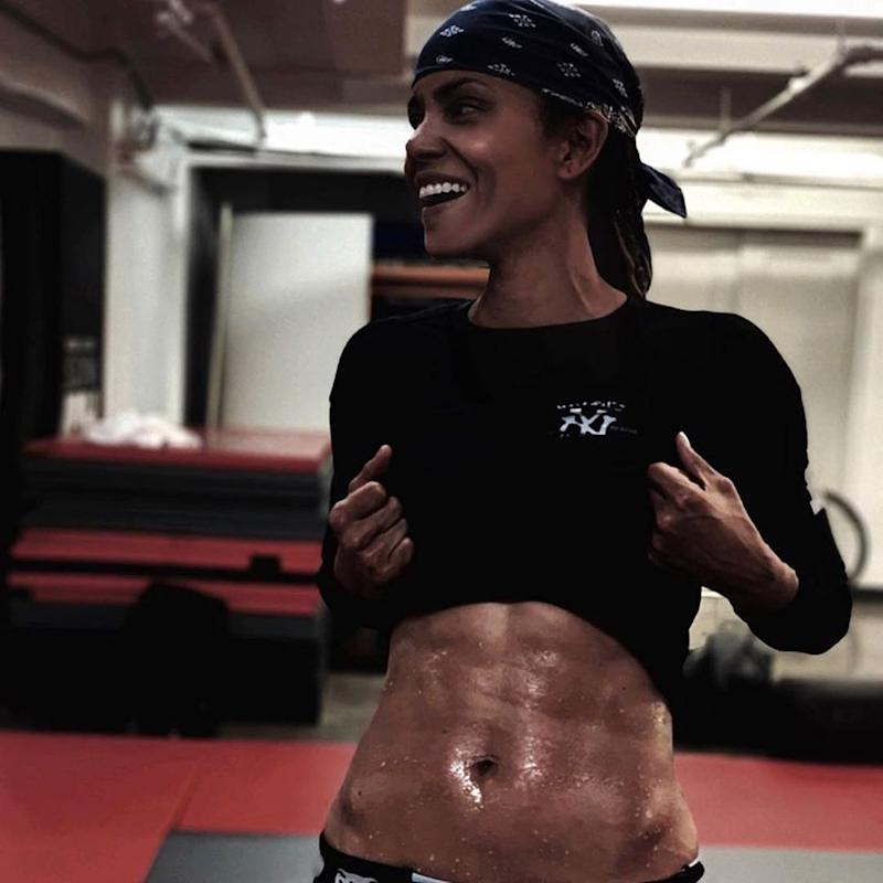 Halle Berry lifts her shirt to showcase her abs