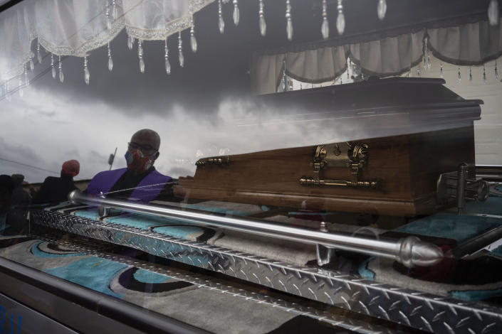 A funeral worker is reflected in the window of the car that carries 5-year-old Wandi Zitho's coffin in Orange Farm, South Africa, on April 28, 2020. The neighbor originally charged with killing the boy was released and the case provisionally dropped because the police didn't deliver enough evidence. Months later, the woman was arrested again and charged with murdering two other children. (AP Photo/Bram Janssen)