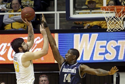 West Virginia's Deniz Kilicli, left, shoots over Georgetown's Henry Sims (14) in the first half of an NCAA college basketball game at WVU Coliseum in Morgantown, W.Va., on Saturday, Jan. 7, 2012. (AP Photo/David Smith)