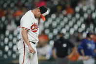 Baltimore Orioles relief pitcher Travis Lakins Sr. reacts after allowing an RBI single by Tampa Bay Rays' Brandon Lowe that scored Randy Arozarena during the sixth inning of a baseball game, Tuesday, May 18, 2021, in Baltimore. (AP Photo/Julio Cortez)
