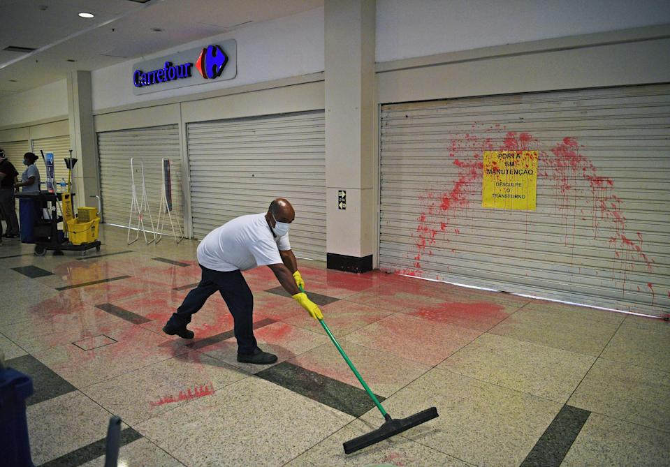 Workers clean up red paint thrown at the entrance of supermarket Carrefour by demonstrators during a protest against the death of a black man inside the supermarket Carrefour, in Rio de Janeiro, on November 22, 2020. - The death of Joao Alberto Silveira Freitas on the night of November 19 after being beaten by white security agents in a supermarket belonging to the Carrefour group in Porto Alegre unleashed a wave of indignation in Brazil. (Photo by CARL DE SOUZA / AFP) (Photo by CARL DE SOUZA/AFP via Getty Images)