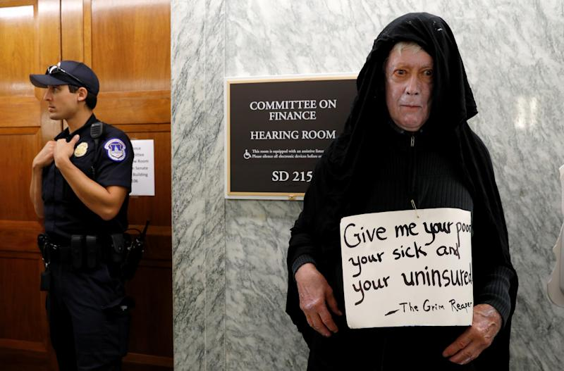 A protester dressed as the grim reaper stands outside the Senate Finance Committee hearing room Monday hours ahead a hearing on the latest effort to repeal Obamacare on Capitol Hill in Washington. (Kevin Lamarque / Reuters)