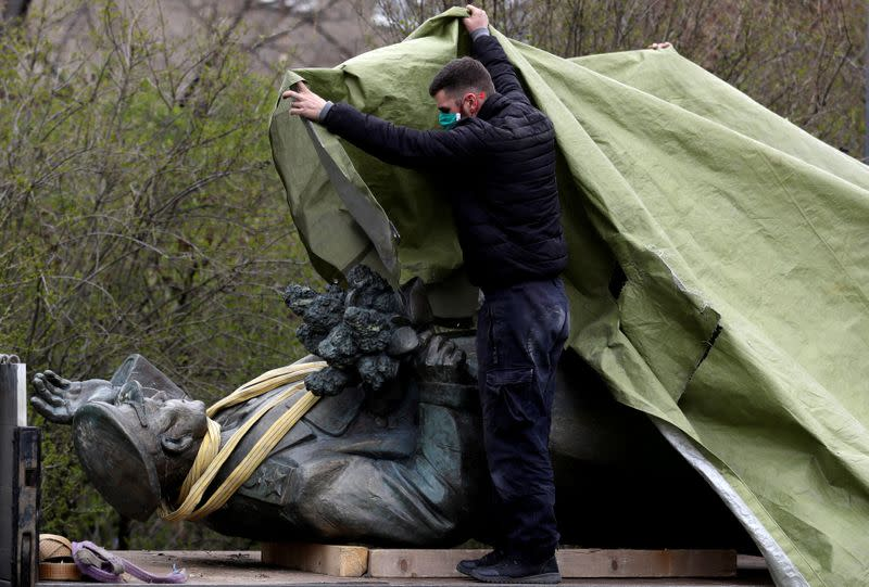 FILE PHOTO: A worker covers the statue of Soviet World War II commander Ivan Stepanovic Konev after removal from its platform in Prague