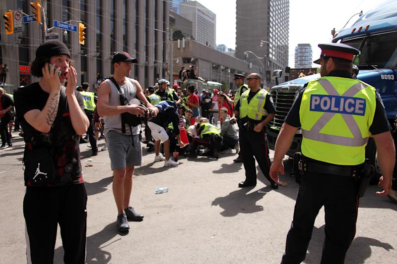 TORONTO, ON - JUNE 17: Police officers attend to an injured person after a shooting occurred during the Toronto Raptors Championship Victory Parade on June 17, 2019 in Toronto, Ontario. According to Toronto Police, Four people were reportedly injured in a shooting during the victory parade at Nathan Philip's square. None of the injuries were life threatening, three people were arrested and two firearms recovered. (Photo by Yu Ruidong/China News Service/VCG via Getty Images)