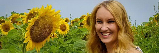 A picture of the writer standing next to a sunflower in a field.