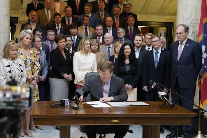 Mississippi Gov. Tate Reeves signs the first state bill in the U.S. this year to ban transgender athletes from competing on female sports teams, as supporting lawmakers gather behind him, Thursday, March 11, 2021, at the Capitol in Jackson, Miss. (AP Photo/Rogelio V. Solis)