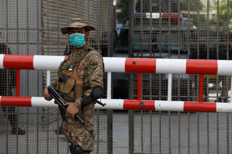 Army soldier wears protective mask as he stands guard at the entrance of the Pakistan Stock Exchange, day after an attack in Karachi