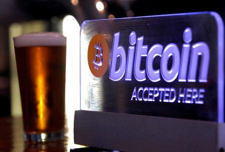 FILE PHOTO: A beer sits next to a Bitcoin sign on display at a bar in central Sydney, Australia, September 29, 2015.  REUTERS/David Gray/File Photo