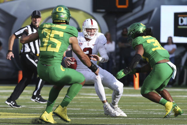 Stanford quarterback K.J. Costello, center, is cornered for a loss by Oregon's Troy Dye, left, and Kaulana Apelu, right, during the first quarter of an NCAA college football game Saturday, Sept. 22, 2018, in Eugene, Ore. (AP Photo/Chris Pietsch)