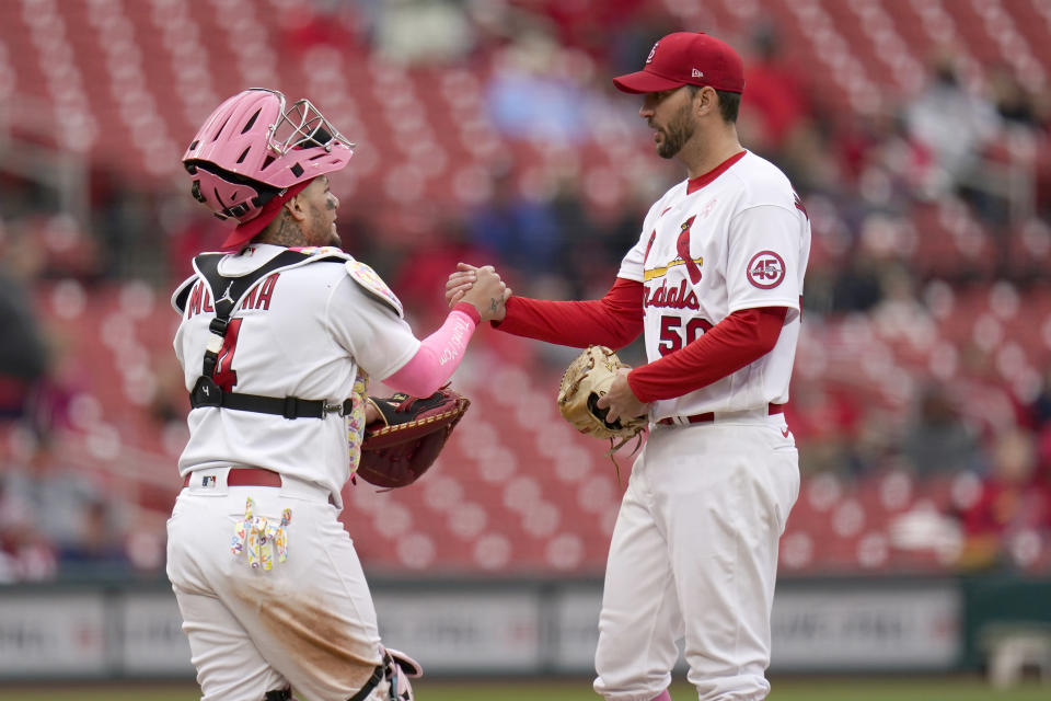 St. Louis Cardinals starting pitcher Adam Wainwright, right, is congratulated by teammate Yadier Molina before being removed during the ninth inning of a baseball game against the Colorado Rockies Sunday, May 9, 2021, in St. Louis. (AP Photo/Jeff Roberson)