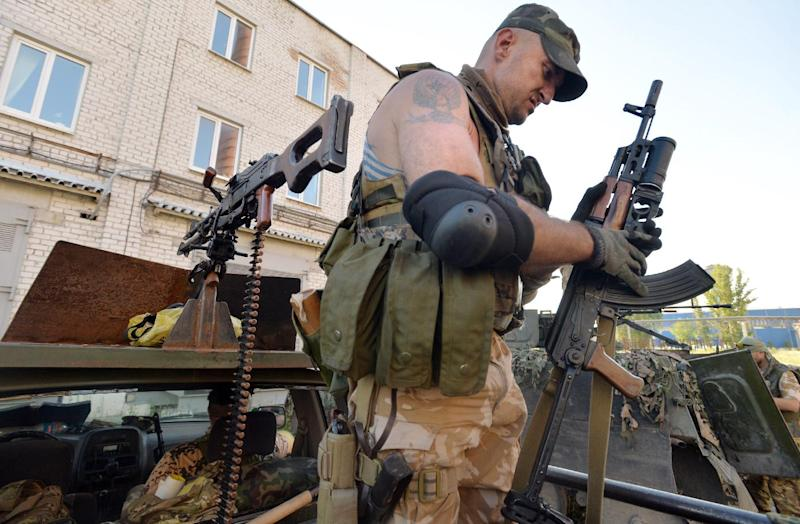 A member of the pro-Ukraine Donbass Battalion checks an automaric rifle seized from pro-Russians, while patroling the outskirts of the eastern Ukrainian city of Lysychansk on July 26, 2014 (AFP Photo/Genya Savilov )