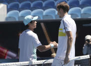 Russia's Daniil Medvedev, right, shakes hands with United States' Mackenzie McDonald after Medvedev won their fourth round match at the Australian Open tennis championships in Melbourne, Australia, Monday, Feb. 15, 2021. (AP Photo/Hamish Blair)