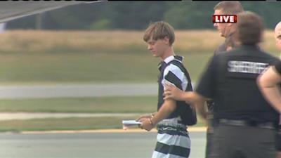 Shooting suspect Dylann Roof being escorted by police to an airplane in Shelby, N.C. (WBTV via AFP)
