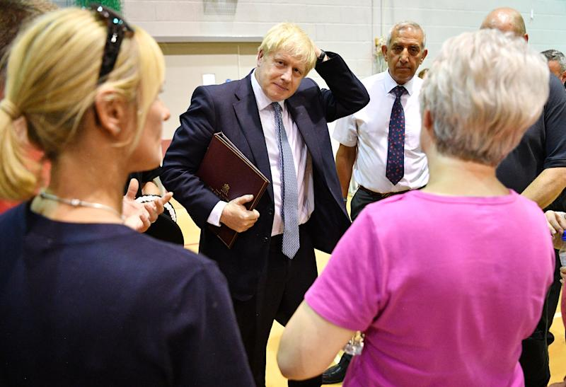 Britain's Prime Minister Boris Johnson meets with rescue crews and local residents at Chapel-en-Le-frith High School as work continues at Toddbrook reservoir in Whaley Bridge, following a severe structural failure after heavy rain, in Britain August 2, 2019. Leon Neal/Pool via REUTERS