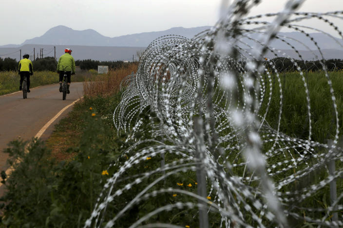 """Two men cylce along a row of razor wire along the southern side of a U.N buffer zone that cuts across the ethnically divided Cyprus, during sunset near village of Astromeritis, Tuesday, March 9, 2021. The government of ethnically split Cyprus has come under fire over a decision to lay razor wire along a section of a U.N. controlled buffer zone it said is needed to stem migrant inflows from the island's breakaway north, with critics charging that the """"ineffective"""" scheme only feeds partitionist perceptions amid a renewed push resume dormant peace talks. (AP Photo/Petros Karadjias)"""
