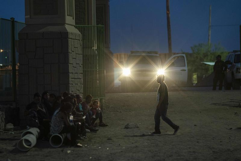 In this file photo taken on May 31, 2019 migrants are pictured waiting to be taken to a processing facility near the Paso Del Norte International Bridge in Downtown El Paso, Texas. -