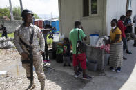 Haitian migrants deported from the US gather after landing at the Toussaint Louverture International Airport in Port-au-Prince, Haiti, Sunday, Sept. 19, 2021. Thousands of Haitian migrants have been arriving to Del Rio, Texas, to ask for asylum in the U.S., as authorities begin to deported them to back to Haiti which is in a worse shape than when they left. (AP Photo/Rodrigo Abd)