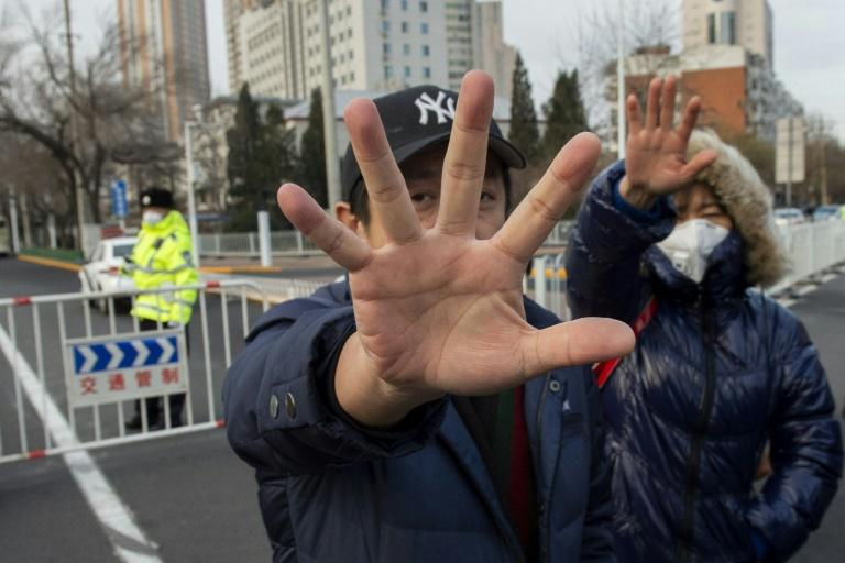 Plainclothes police officers stop photographs outside the court where the human rights lawyer Wang Quanzhang was tried in December 2018