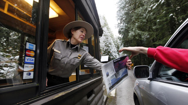 Mount Rainier National Park Ranger Judy Scavone hands park information to visitors in 2012. (Photo: Elaine Thompson/AP)