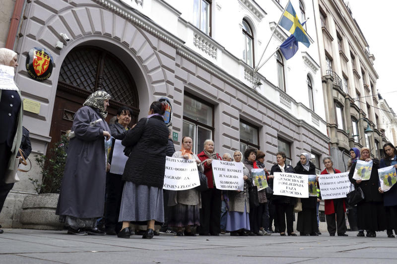 Bosnian women whose male family members, including sons and husbands, perished in the Srebrenica massacre hold placards as they protest outside Swedish embassy in Sarajevo, Bosnia-Herzegovina, Tuesday, Nov. 5, 2019. Several dozen survivors of Bosnia's 1992-95 war staged a protest in Sarajevo to call on the Nobel Committee to reverse its decision to award the 2019 Nobel Prize in literature to Austria's Peter Handke. Placards read: 'to award Handke is equal awarding committed crime' and 'award for Hadke is award for Slobodan Milosevic'. Despite a U.N. court ruling to the contrary, Handke has persistently denied that genocide took place in Srebrenica. (Almir Razic/Fena Agency via AP)