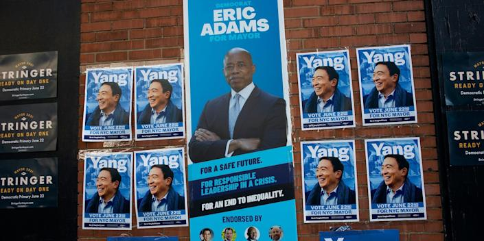 posters for new york city mayor candidates andrew yang, scott stringer, and eric adam