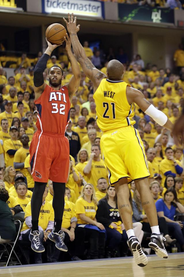Atlanta Hawks forward Mike Scott (32) shoots over Indiana Pacers forward David West (21) during the first half of Game 7 of a first-round NBA basketball playoff series in Indianapolis, Saturday, May 3, 2014. (AP Photo/AJ Mast)