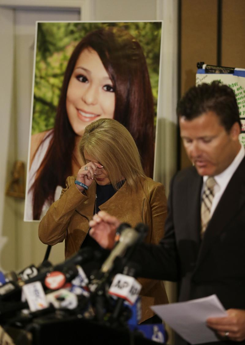 Sheila Pott, wipes her eyes standing in front of a photograph of her daughter Audrie Pott,  who committed suicide after a sexual assault as family representative Robert Allard, right, reads a statement during a news conference Monday, April 15, 2013 in San Jose, Calif. The family of a girl who committed suicide after she was sexually assaulted and a photo of the act was shared in text messages said Monday the three 16-year-old boys responsible were sober when the assault happened. They said they were outraged by what they see as a refusal to take responsibility by the three boys arrested in the attack on the 15-year-old girl in Saratoga, a bedroom community on the fringe of Silicon Valley. (AP Photo/Eric Risberg)