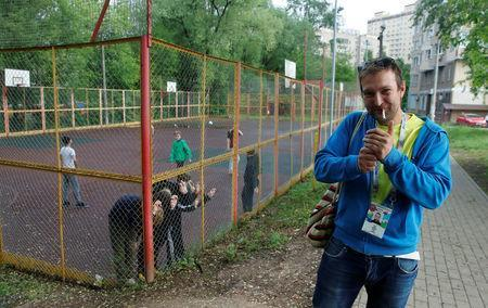 Soccer fan Pavel Cherkas, who was blacklisted by Russian authorities for bad behaviour at a stadium, smokes a cigarette while wearing his 2018 World Cup fan ID, which was granted to Cherkas and later revoked, during an interview outside Moscow, Russia May 20, 2018. REUTERS/Maxim Shemetov