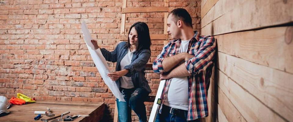 Couple looking at blueprint for home in room under construction.