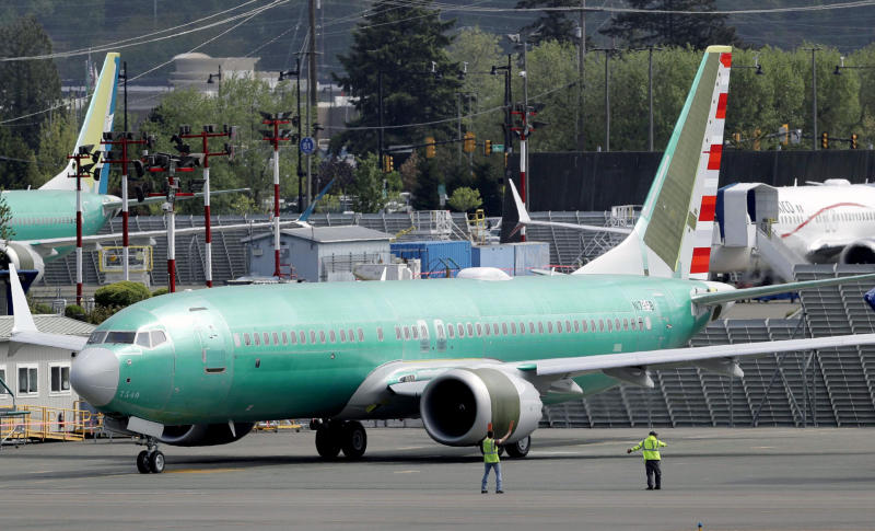 FILE - In this May 8, 2019, file photo workers stand near a Boeing 737 MAX 8 jetliner being built for American Airlines prior to a test flight in Renton, Wash. American Airlines CEO Doug Parker says his airline is feeling more confident that its grounded Boeing 737 Max jets will soon be approved to fly again. (AP Photo/Ted S. Warren, File)