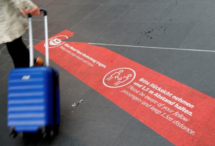 FILE PHOTO: A social distancing floor sign is seen at the main train station Hauptbahnhof, as the spread of the coronavirus disease (COVID-19) continues, in Berlin